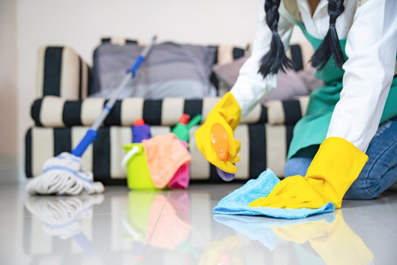 Husband housekeeping and cleaning concept, Happy young Woman in blue rubber gloves wiping dust using a spray and a duster while cleaning on floor at home