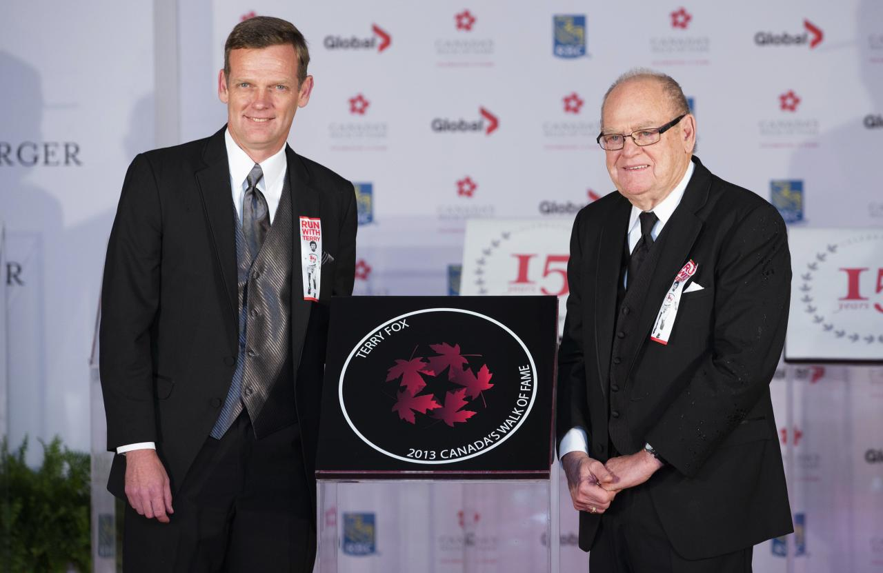 Late cancer research advocate Terry Fox has his star accepted posthumously by his brother Darrell Fox and his father Rolly Fox (R) during Canada's Walk of Fame induction ceremonies in Toronto, September 21, 2013. REUTERS/Mark Blinch (CANADA - Tags: ENTERTAINMENT HEALTH SCIENCE TECHNOLOGY)