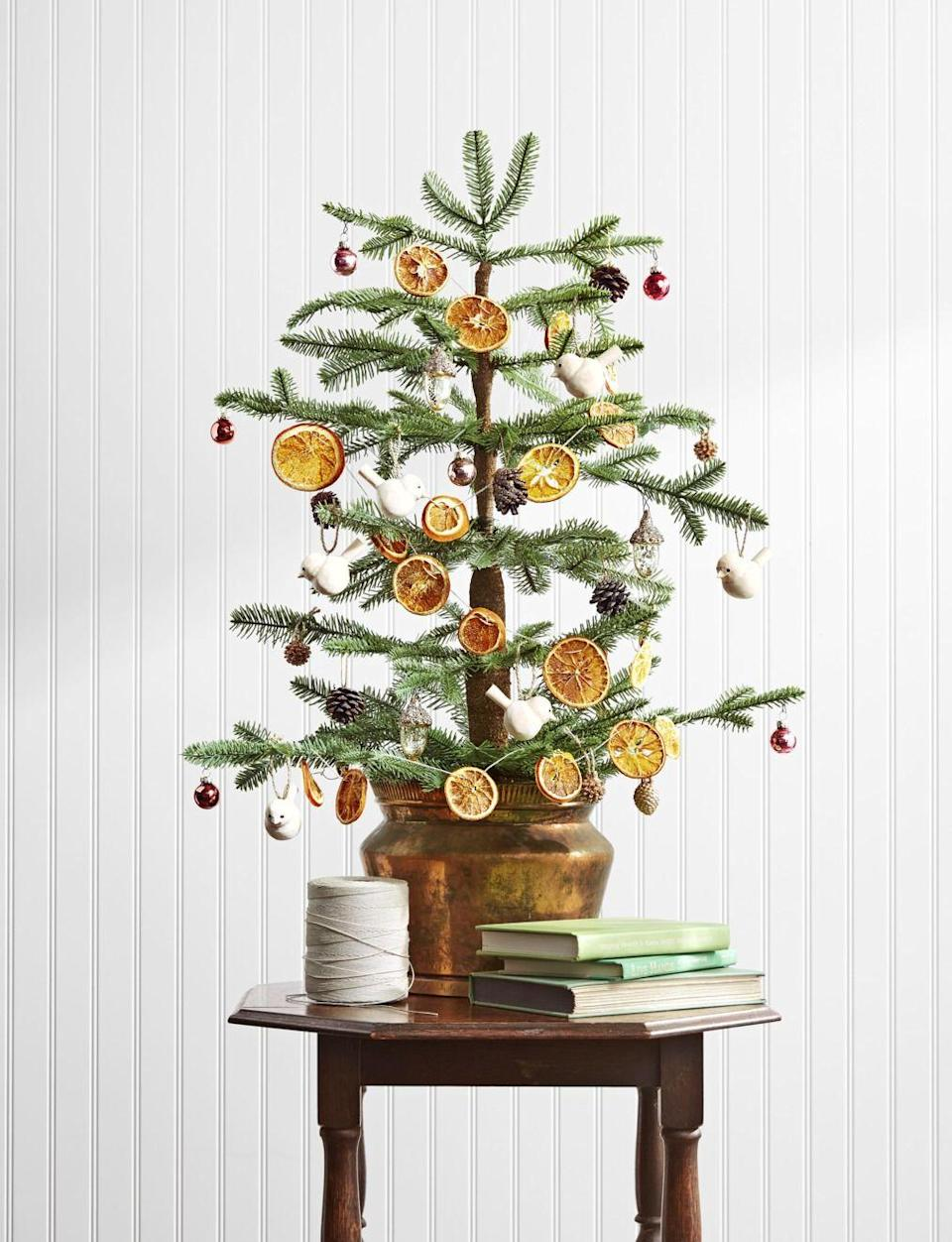 """<p>Citrus ornaments look almost like stained glass when the light shines through them. To string your own strand, all you need are navel and blood oranges, parchment paper, two cookie sheets, jute or natural twine, a skewer or nail, and decorative hooks. </p><p><strong>Make the Ornaments:</strong></p><p>1. Preheat oven to 250°F. </p><p>2. Cut oranges crosswise into 1/4-inch slices (four oranges make a six-foot garland). </p><p>3. Line cookie sheets with parchment paper. Pat orange slices dry with paper towels, and place them on cookie sheets in a single layer. </p><p>4. Bake for approximately 3 hours or until dry. (To ensure the slices dry flat, turn them over at the midway mark.) Remove from oven. </p><p>5. Using a skewer or nail, poke two holes into the top of each orange slice. </p><p>6. Thread twine through each hole, evenly spacing the oranges on the garland. Tie off each end with a loop, and hang from hooks.</p><p><a class=""""link rapid-noclick-resp"""" href=""""https://www.amazon.com/çokçerez-Dried-orange-slices-cokcerez/dp/B092JK1Y4K/ref=sr_1_1_sspa?tag=syn-yahoo-20&ascsubtag=%5Bartid%7C10050.g.1070%5Bsrc%7Cyahoo-us"""" rel=""""nofollow noopener"""" target=""""_blank"""" data-ylk=""""slk:SHOP DRIED ORANGE SLICES"""">SHOP DRIED ORANGE SLICES</a></p>"""