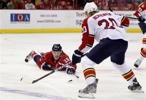 Washington Capitals left wing Alexander Semin (28), of Russia, dives for the puck in front of Florida Panthers left wing Sean Bergenheim (20) during the first period of an NHL hockey game Thursday, April 5, 2012, in Washington. (AP Photo/Evan Vucci)