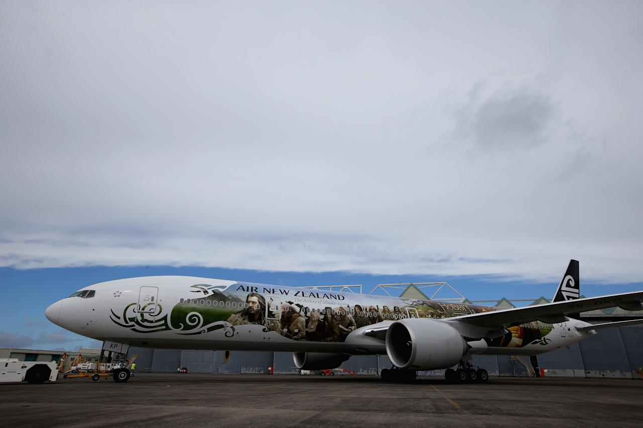 """AUCKLAND, NEW ZEALAND - NOVEMBER 24:  Air New Zealand unveils a 777-300 aircraft with imagery from The Hobbit ahead of the """"The Hobbit: An Unexpected Journey"""" world premiere at Auckland International Airport on November 24, 2012 in Auckland, New Zealand.The imagery depicts characters from the upcoming film and extends the full 73 metre length of the aircraft.  (Photo by Phil Walter/Getty Images)"""