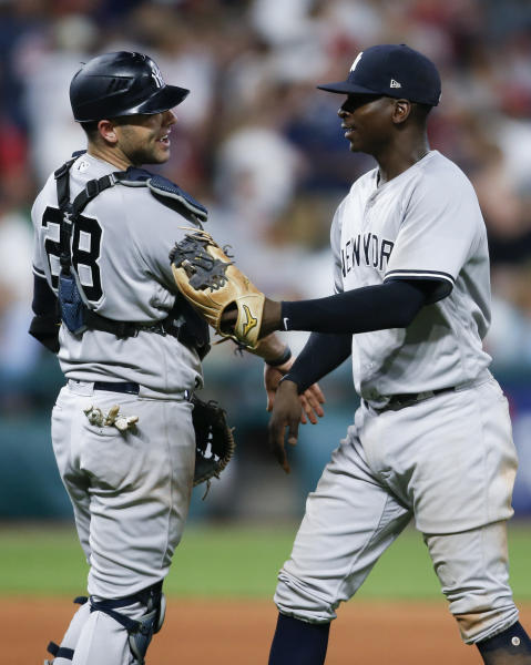 New York Yankees' Didi Gregorius, right, and Austin Romine (28) celebrate a victory over the Cleveland Indians in a baseball game, Saturday, July 14, 2018, in Cleveland. (AP Photo/Ron Schwane)