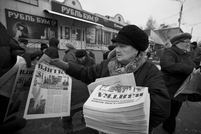 In this Nov. 14, 2012, photo, a woman hands out copies of the news paper Bribe in Cheboksary, the capital city of Chuvashia, Russia. Eduard Mochalov has found a new lease on life as a crusading journalist investigating corruption in his native region, fueled by tips from disgruntled businessmen and government workers. Undeterred by a system where the law is selectively used to protect the powerful and crack down on critics, Mochalov has quickly earned cult status _ not to mention the ire of countless local officials _ throughout the small province of Chuvashia. (AP Photo/Alexander Zemlianichenko)