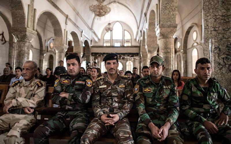 Iraqi Christian soldiers attend an Easter ceremony at Saint John's Church in Qaraqosh, near Mosul - Credit: Carl Court/Getty
