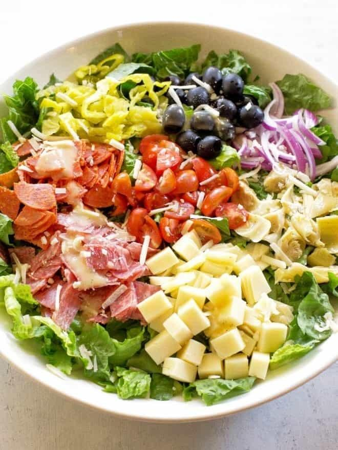 A salad with salami, provolone, artichoke, tomatoes, and more.