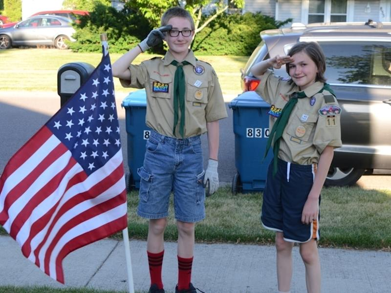"""Grayson Arndt, left, and Seth Arndt, of Oswego, salute Sunday at dusk before removing a flag as part of the troop's """"Post the Colors"""" fundraiser."""