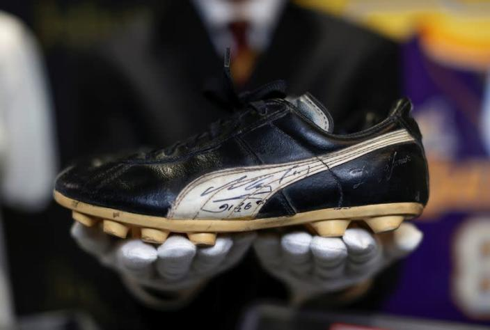 """Kendall Capps holds a pair of soccer boots worn and autographed by late soccer star Diego Armando Maradona ahead of the upcoming """"Sports: Legends"""" auction in Culver City"""