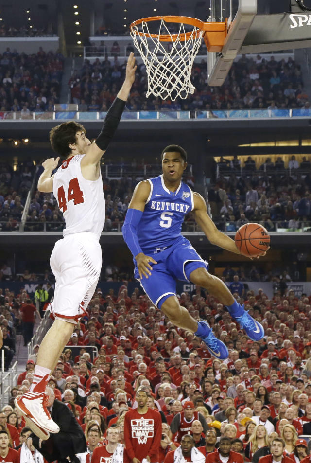 Kentucky guard Andrew Harrison, right, drives to the basket past Wisconsin forward Frank Kaminsky during the first half of the NCAA Final Four tournament college basketball semifinal game Saturday, April 5, 2014, in Arlington, Texas. (AP Photo/Eric Gay)