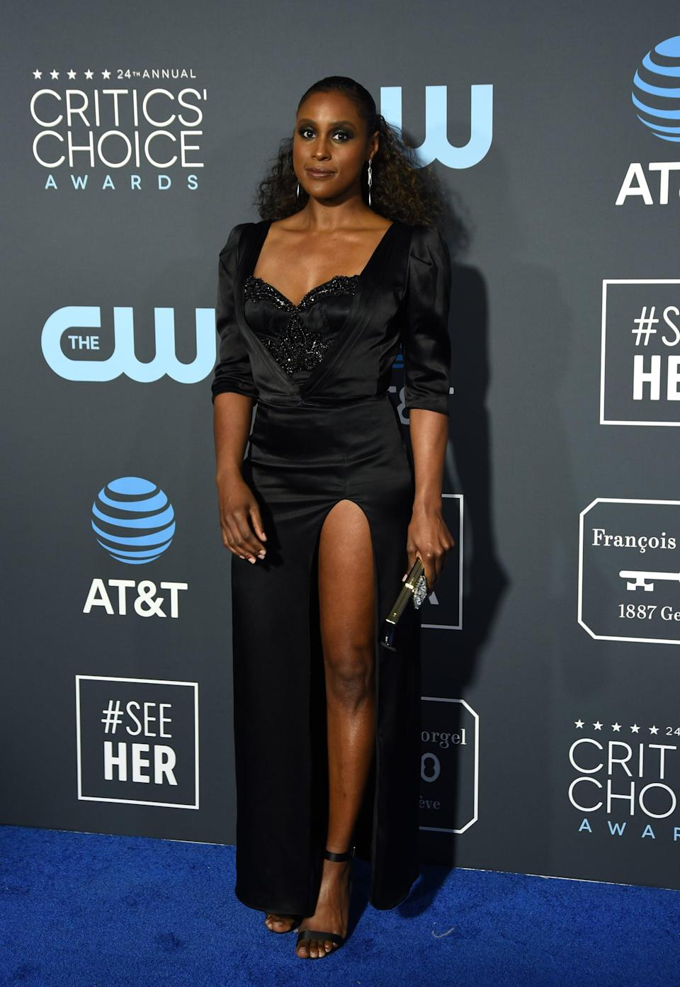 <p>Issa Rae wearing a black dress with a daring thigh-high slit by Aliétte by Jason Rembert. She accessorized with Lorraine Schwartz jewels and Tamara Mellon heels.</p>