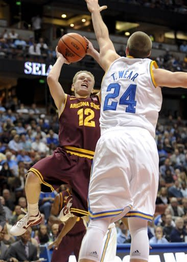 Arizona State guard Max Heller (12) attempts to get a shot off as he drives on UCLA forward Travis Wear (24) during the first half of an NCAA college basketball game, Saturday, Jan. 7, 2012, in Anaheim, Calif. (AP Photo/Gus Ruelas)