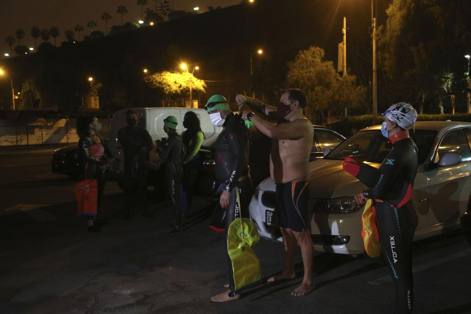Open water swimmers get ready by their cars on Pescadores beach where open water swimming is booming while pools are closed due to the COVID-19 pandemic in Lima, Peru, before sunrise Tuesday, April 27, 2021. One of the few sporting disciplines that have been maintained during the coronavirus pandemic is swimming, which due to the closure of the swimming pools, has moved to the open sea. (AP Photo/Martin Mejia)