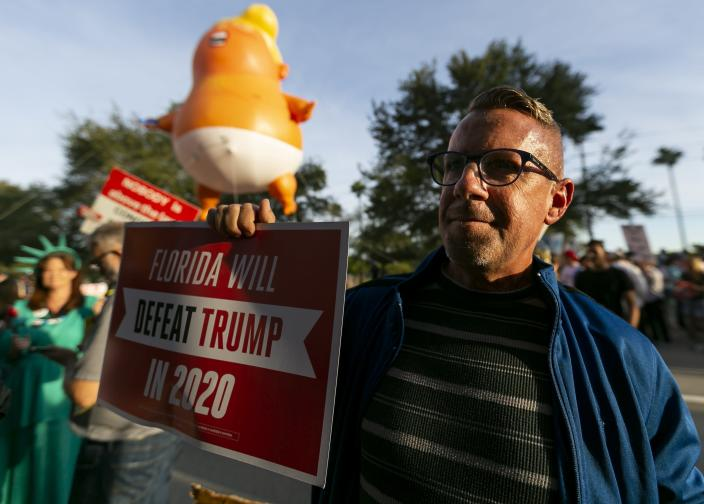 """Dennis Becker, 54, from Fort Lauderdale, gathers near the BB&T Center with a giant inflatable baby of President Donald Trump before a """"homecoming"""" rally in Sunrise, Florida on Tuesday, Nov. 26, 2019. The rally is being held in celebration of Donald Trump's decision to change his full-time residence from Manhattan to Palm Beach. (Matias J. Ocner/Miami Herald via AP)"""