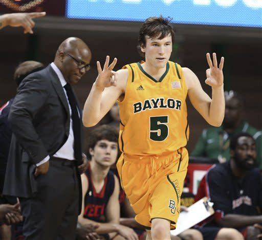 Baylor's Brady Heslip gestures after his 3-point basket against Texas Tech in the first half of an NCAA college basketball game, Saturday, Feb. 9, 2013, in Waco, Texas. At left is Texas Tech coach Chris Walker. (AP Photo/Waco Tribune Herald, Rod Aydelotte)