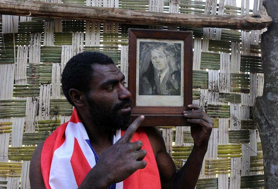 Sikor Natuan, the son of the local chief, holds a water damaged portrait of Britain's Prince Philip in a partially built monument to the British royal near the remote village of Yaohnanen on Tanna in Vanuatu on August 6, 2010. In his remote village in Vanuatu, tribesman Sikor Natuan cradles a faded portrait of Britain's Prince Philip against his naked and tattooed chest. Natuan, who just weeks before danced and feasted to mark the royal's 89th birthday, is already preparing for next year's celebrations -- and he is expecting the guest of honour to attend, despite his advanced age. For in the South Pacific village of Yaohnanen on Vanuatu's Tanna island, where men wear nothing but grass penis sheaths, and marijuana and tobacco grow wild, Prince Philip is worshipped as a god.