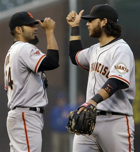San Francisco Giants closer Sergio Romo, left, celebrates with shortstop Brandon Crawford after they defeated the Chicago Cubs 7-6 in a baseball game in Chicago, Thursday, April 11, 2013. (AP Photo/Nam Y. Huh)