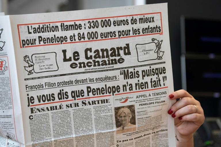 "A journalist reads ""Le Canard Enchaine"", the satirical newspaper that first reported Francois Fillon allegedly giving his wife fake jobs as a parliamentary assistant"