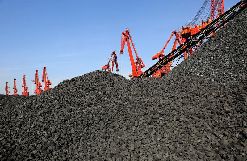 Cranes unload coal from a cargo ship at a port in Lianyungang