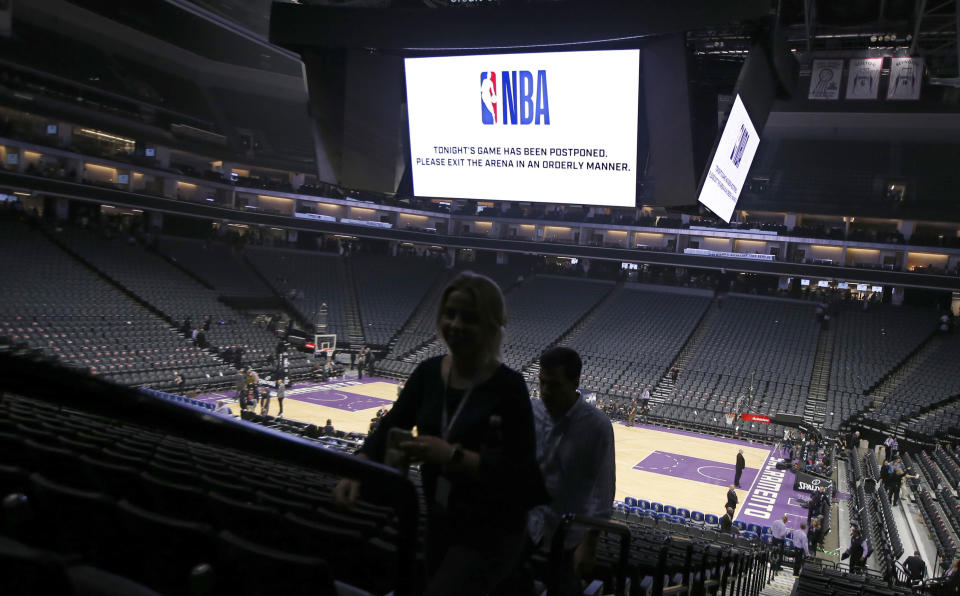 FILE - In this March 11, 2020, file photo, fans leave the Golden 1 Center after the NBA basketball game between the New Orleans Pelicans and Sacramento Kings in Sacramento, Calif., was postponed at the last minute due to the coronavirus. A year after the worldwide coronavirus pandemic stopped all the games in their tracks, the aftershocks are still being felt across every sector. (AP Photo/Rich Pedroncelli, File)