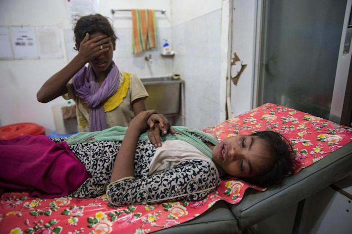 <p>Kajal Nur, 11, is treated for injuries from a road traffic accident as her friend tries to comfort her at the 'Doctors Without Borders' Kutupalong clinic on October 4, 2017 in Cox's Bazar, Bangladesh. (Photograph by Paula Bronstein/Getty Images) </p>