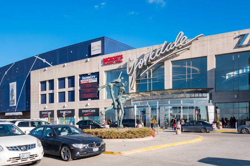 Toronto, Canada - April 5, 2014: People enter and exit the Yorkdale Shopping Centre with parked cars in the foreground. The mall is one of the largest in Toronto and celebrates its 50th year anniversary in 2014.