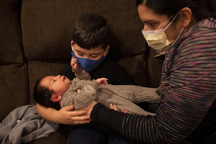 A woman in a mask puts a newborn boy in the arms of a toddler, also wearing a mask