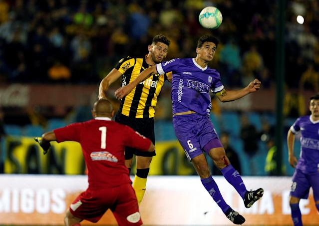 Soccer Football - Uruguayan Championship - Defensor Sporting v Penarol - Centenario stadium, Montevideo, Uruguay - December 10, 2017. Penarol's Yeferson Quintana and Defensor Sporting Gaston Rodriguez and Andres Lamas in action. REUTERS/Andres Stapff