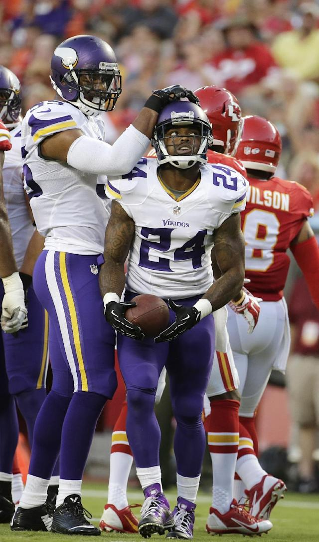 Minnesota Vikings linebacker Anthony Barr, left, congratulates cornerback Captain Munnerlyn (24) who intercepted in the end zone during the first half of an NFL preseason football game against the Kansas City Chiefs in Kansas City, Mo., Saturday, Aug. 23, 2014. (AP Photo/Charlie Riedel)