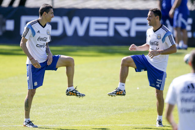 Argentina's Angel di Maria, left, talks to teammate Maxi Rodriguez as they warm up during a training session in Vespasiano, near Belo Horizonte, Brazil, Friday, June, 13, 2014. Argentina will play in group F of the Brazil 2014 soccer World Cup. (AP Photo/Victor R. Caivano)