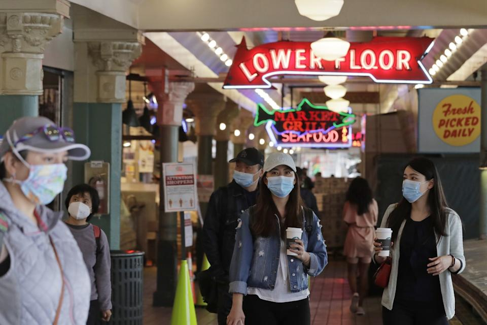 People wear masks as they walk through Pike Place Market in Seattle