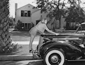 <p>Singer and actress Garland gives her 1939 Packard Six some special attention during the filming of the <em>The Wizard of Oz—</em>the musical that became one of her career's crowning achievements. <br></p>