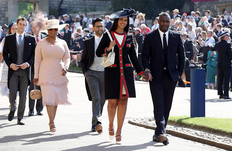 Idris Elba and Sabrina Dhowre followed by Oprah Winfrey (fourth right) arrive at St George's Chapel at Windsor Castle for the wedding of Meghan Markle and Prince Harry on May 19, 2018 in Windsor, England.