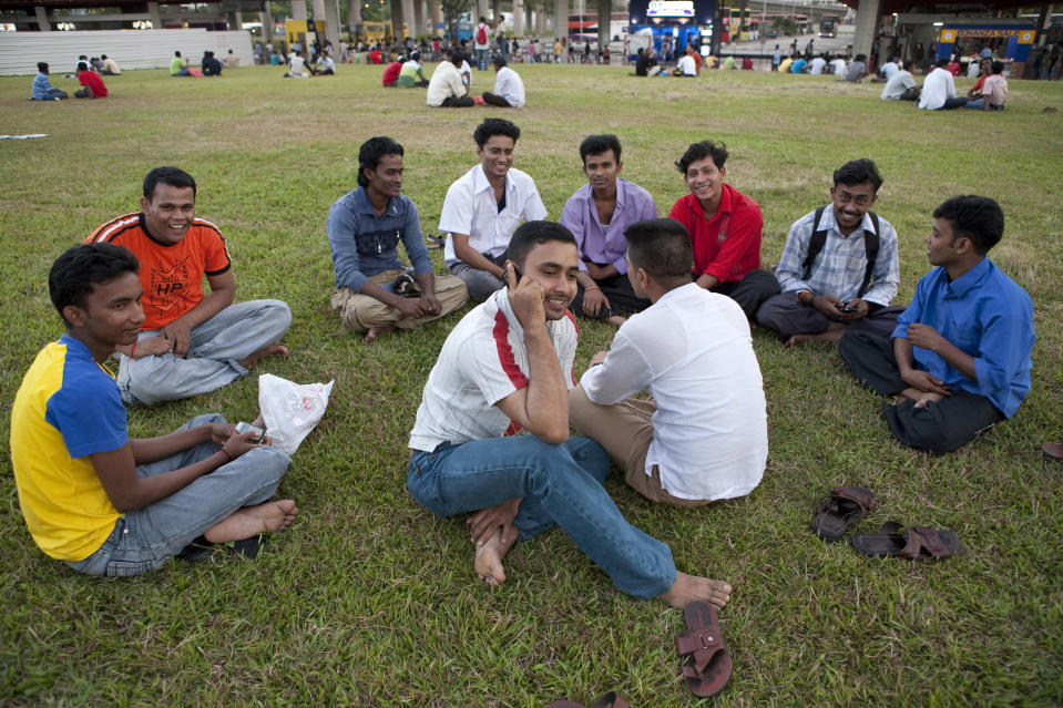 A group of foreign workers chat on a grass field during their day off outside a bus interchange in Singapore on 18 January, 2009. (Reuters file photo)