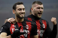 AC Milan's Hakan Calhanoglu, left, celebrates with his teammate AC Milan's Ante Rebic, his goal against Lazio during a Serie A soccer match between AC Milan and Lazio, at the San Siro stadium in Milan, Italy, Wednesday, Dec. 23, 2020. (AP Photo/Luca Bruno)