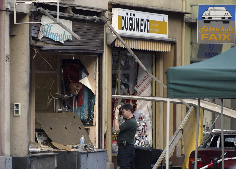 FILE - In this June 9, 2004 file photo a policeman takes pictures of a bombed barber's shop in Cologne, western Germany. The verdict against the only surviving member and supporters of the far-right cell NSU is expected on Wednesday, July 11, 2018. The cell calling itself the National Socialist Underground allegedly targeted migrants, killing 10 people between 2000 and 2007. (AP Photo/Martin Meissner, file)