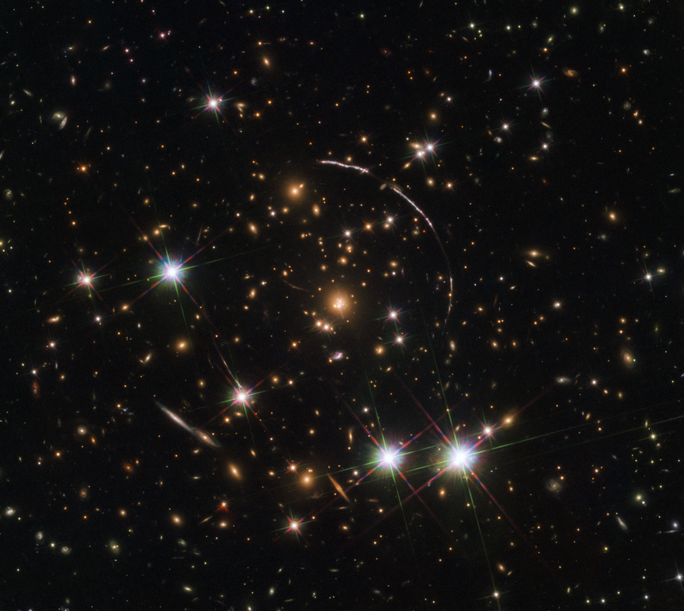 "When the Hubble Space Telescope turned its gaze toward the remote galaxy known as the ""Sunburst Arc,"" it saw not one but 12 separate images of the lone cosmic object. That's because there's a massive galaxy cluster in the foreground warping the light with its intense gravitational pull. This illusion is known as gravitational lensing, a phenomenon that Albert Einstein first described in his theory of general relativity. ""This 'funhouse mirror' effect not only stretches the background galaxy image, but also creates multiple images of the same galaxy,"" NASA officials said in a statement."