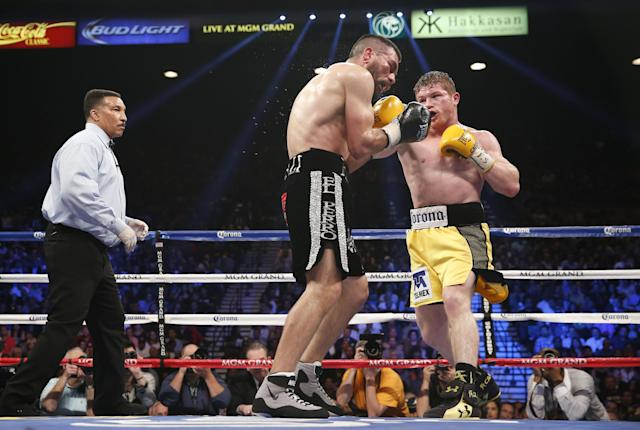 Referee Tony Weeks watches as Saul Alvarez of Guadalajara Mexico, right, trades punches with Alfredo Angulo of Mexicali Mexico during their super welterweight boxing match, Saturday, March 8, 2014, at The MGM Grand Garden Arena in Las Vegas. Alvarez won by TKO when the fight was stopped by referee Tony Weeks. (AP Photo/Eric Jamison)