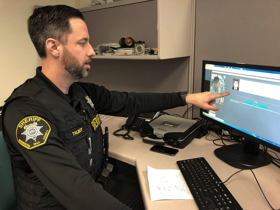FILE - In this Feb. 22, 2019, file photo, Washington County Sheriff's Office Deputy Jeff Talbot demonstrates how his agency used facial recognition software to help solve a crime, at their headquarters in Hillsboro, Ore. The image on the left shows a man whose face was captured on a surveillance camera and investigators used the software to scan their database of past mug shots to match that facial image with an identity. Amazon said Wednesday, June 10, 2020, it will ban police use of its facial recognition technology for a year in order to give Congress time to come up with ways to regulate the technology. (AP Photo/Gillian Flaccus, File)