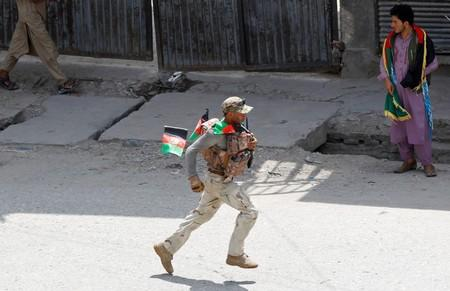 A member of Afghan security forces runs after a blast in Jalalabad