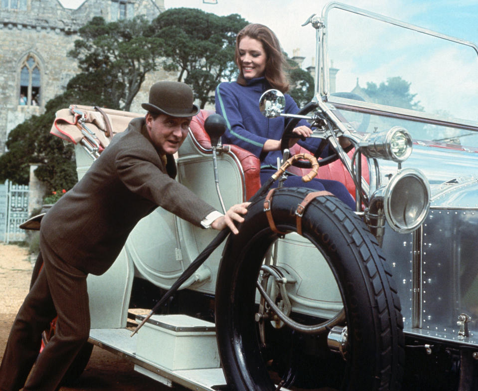 """Diana Rigg as Mrs. Emma Peel on the British spy series, """"The Avengers."""" She is shown at the wheel of a car which is being pushed by co-star Patrick MacNee (John Steed). The television series originated in 1961, but ran in the U.S. from 1966 to 1969 on ABC. Color slide circa 1960s"""
