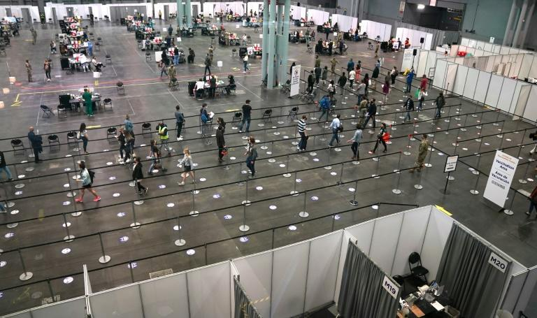 People wait in line at the Jacob K. Javits Convention Center in New York which has been transformed into a Covid-19 vaccination site