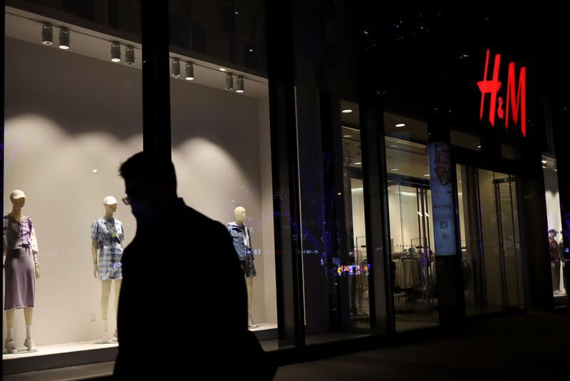 Man walks past an H&M store at a shopping mall in Beijing