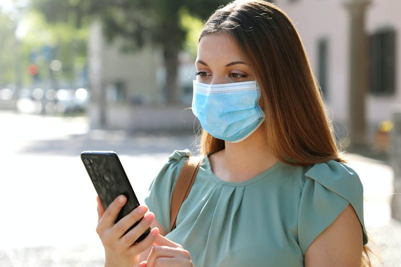 A woman wearing a face mask looks at her mobile phone.