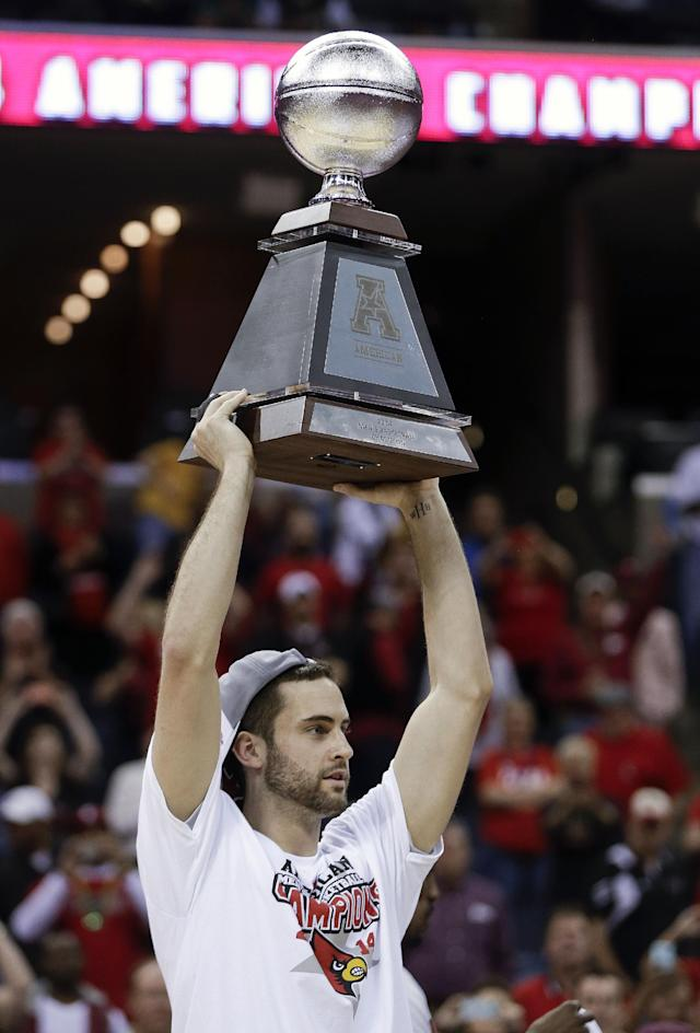 Louisville forward Luke Hancock holds up the championship trophy after Louisville defeated Connecticut in an NCAA college basketball game in the finals of the American Athletic Conference men's tournament Saturday, March 15, 2014, in Memphis, Tenn. Louisville won 71-61. (AP Photo/Mark Humphrey)