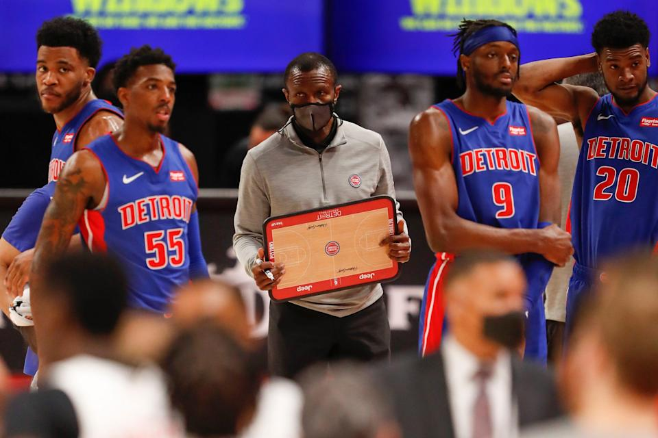 Detroit Pistons forward Saddiq Bey guard Delon Wright (55), head coach Dwane Casey (middle) and forward Jerami Grant (9) stand on the court during a timeout March 17, 2021, against the Toronto Raptors at Little Caesars Arena.