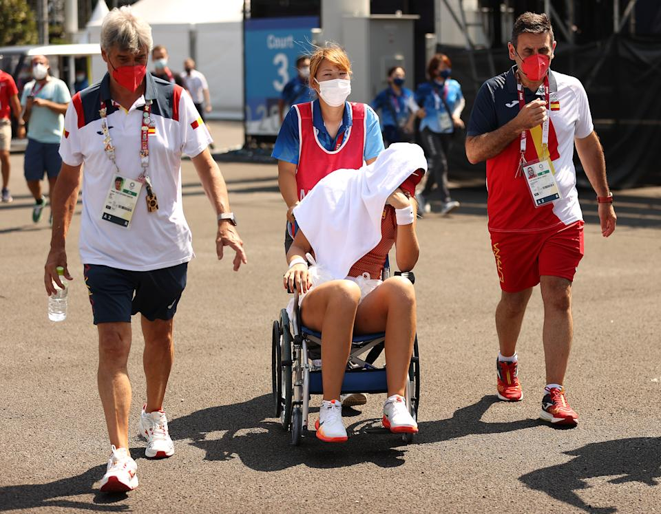 Paula Badosa of Team Spain is helped away from the court in a wheelchair after having to retire from her Women's Singles Quarterfinal match.