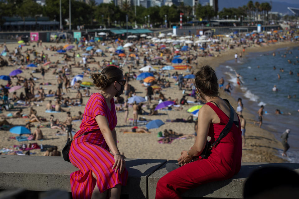 Two women look at the beach in Barcelona, Spain, Saturday, July 18, 2020. Police in Barcelona are closing access to a large area of the city's beaches due to the excess of sunbathers who decided to ignore the urgings of authorities to stay at home amid a resurgence of the coronavirus. (AP Photo/Emilio Morenatti)