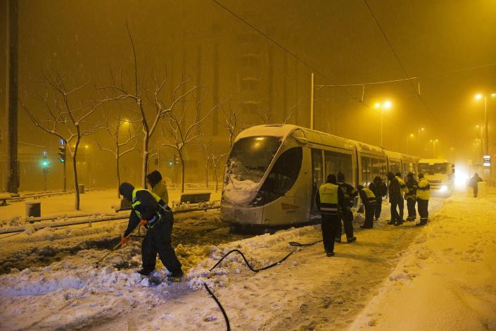 Municipality workers clear snow from the tracks of the light rail tram early morning in Jerusalem February 20, 2015. Snow covered Jerusalem and mountainous areas of Israel early Friday morning and the education ministry closed schools for the day. (REUTERS/Ronen Zvulun)