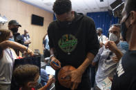 NBA Champion Giannis Antetokounmpo, of the Milwaukee Bucks, who was named NBA Finals Most Valuable Player, signs an autograph at the Eleftherios Venizelos International Airport, in Athens, Greece, Sunday, Aug. 1, 2021. The NBA champion and finals MVP plans to stay in Greece for a few days, before returning to the U.S., where his girlfriend expects their second child later this month. (AP Photo/Michael Varaklas)