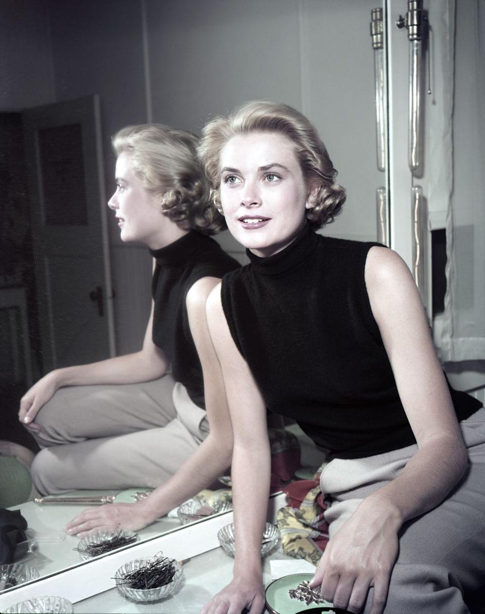<p>Kelly looks chic in a casual black sleeveless turtleneck and tan pants in her dressing room on set in 1954. </p>
