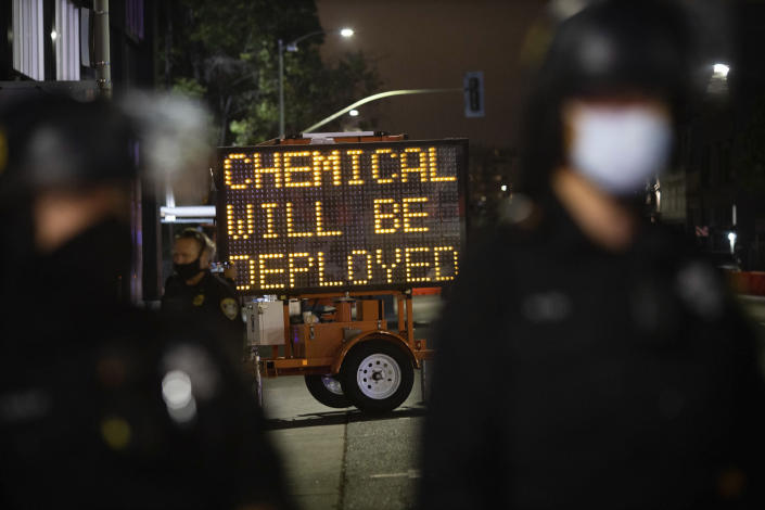 A road sign warns protesters of the use of chemical agents for failure to disperse after a protest was declared unlawful on Saturday, July 25, 2020, in Oakland, Calif. Protesters in California set fire to a courthouse, damaged a police station and assaulted officers after a peaceful demonstration intensified late Saturday, Oakland police said. (AP Photo/Christian Monterrosa)